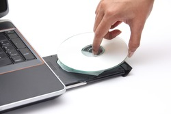 Person placing a CD in a laptop cdrom drive