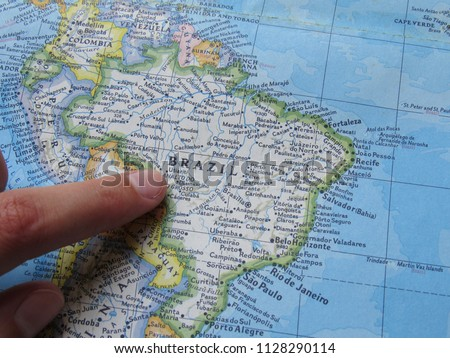 Person pointing at Brazil on a map for planning a vacation  #1128290114