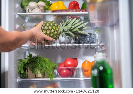 Person putting fresh pineapple into refrigerator full of food #1149621128
