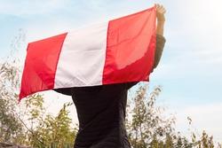 Person raising the flag of Peru