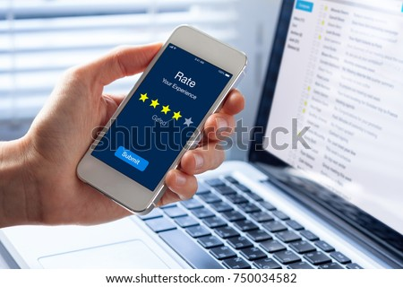 Person rating his experience with 4 stars on smartphone app screen, concept about online customer satisfaction feedback and quality evaluation of service, hotel or restaurant