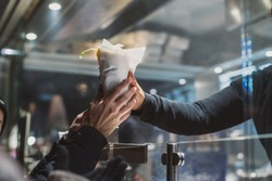 Person receiving a fresh kebab or gyros in a fast food stall or vendor outside in a city. Visible hands exchanging fast food over the counter in festive evening.