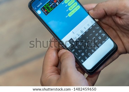 Person receiving and sending encrypted messages on a mobile phone. Alien message concept.