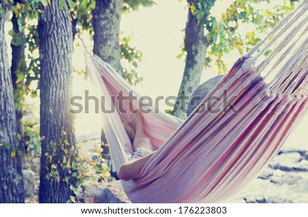 Person relaxing in a hammock in the shade of a tree on a hot summer day view from behind With retro filter effect