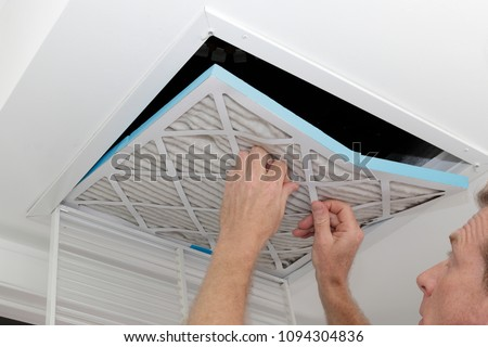 Person removing an old dirty air filter from a ceiling intake vent of a home HVAC system. Unclean gray square furnace air filter being taken out of a ceiling air vent.