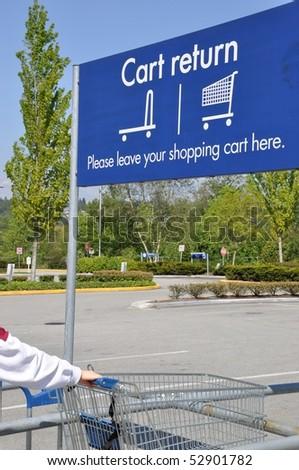 Person return shopping cart with cart reture sign