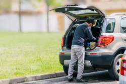 Person returning from shopping with the car wearing blue latex gloves as a measure of protection from the coronavirus. Man with shopping bags coming home during quarantine.