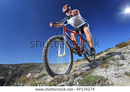 Person riding a bike downhill style #49134274