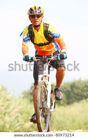 Person riding a bike downhill  to the river