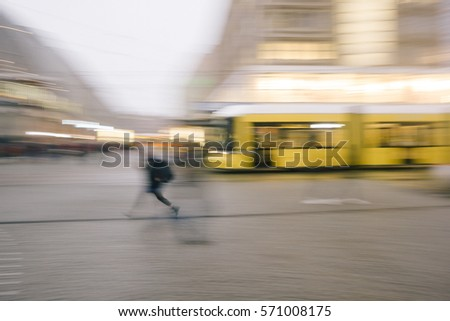 Person running in front of tram, cable car, intentional motion blur for anonymity, concept image of public transport, traffic. #571008175