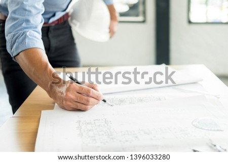 Person's engineer Hand Drawing Plan On Blue Print with architect equipment, Architects working at the table #1396033280