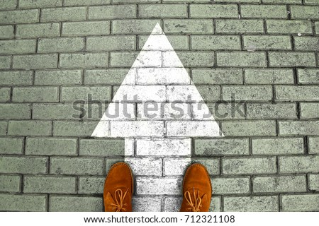 Person's feet in suede shoes is standing at tile pavement crossroad with white arrow print pointing ahead. Only way without choose and making decision which way to go. Top view. Minimalist image #712321108