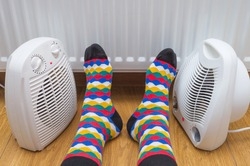 Person's feet near an electric fan heaters and radiator at home. Symbolic image of home heating in the cold winter season. Close-up, selective focus.