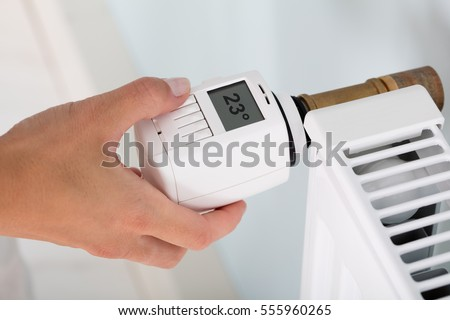 Person's Hand Adjusting Temperature On Thermostat To Control Heat In Central Heating System #555960265
