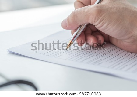 Person's hand hold ballpoint pen writing on blank application form paper sheet: Fill in blank document template applying for job finance loan mortgage, claim for health, HR business, insurance concept