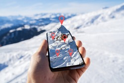 Person's Hand Holding Mobile Phone With Mountain Map Against Blurred Snowy Background