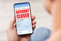 Person's Hand Holding Mobile Phone With Online Banking Application And Account Closed Message On Screen
