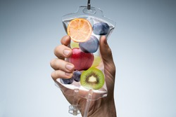 Person's Hand Holding Saline Bag Filled With Various Fruit Slices Against Grey Backdrop