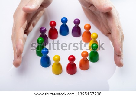 Person's Hand Protecting Multi Colored Pawns Forming Circle Over White Desk #1395157298