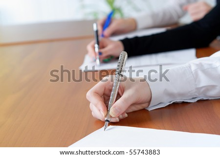 person's hand signing an important document