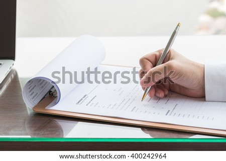 Person\'s hand with ballpoint pen writing on blank application form paper: Fill in empty document template applying for a job, finance, loan, mortgage or a claim for health, business insurance concept
