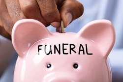Person Saving Money For Funeral By Inserting Coin In Piggy Bank With Funeral Text