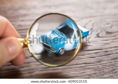 Person Scrutinizing A Car Model Using Magnifying Glass On Wooden Desk #609053510