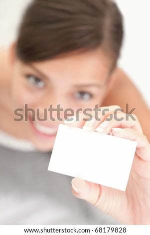 Person showing business card. Casual woman smiling holding the card. Shallow depth of field, focus on paper with empty copy space.