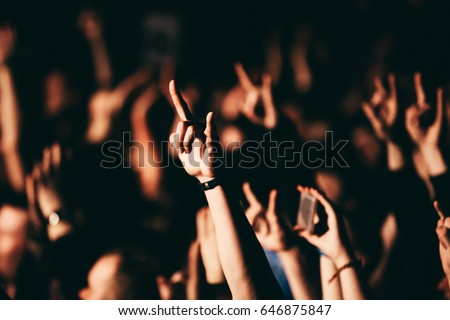 Person showing sign of the horns during a rock band concert in club.  A crowd of people at during a concert. Two finger rock hand.