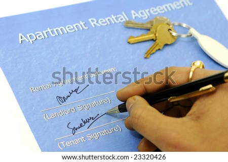 person signing on the cover sheet of a apartment lease document with the house keys in the background
