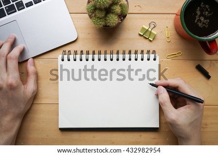 Person sketching or taking note down on blank open notebook with cup of fresh coffee on desk #432982954