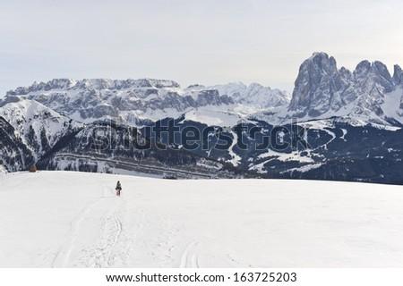 Person snowshoeing against wide Dolomites landscape