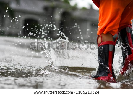 Person splashing with rainboots in a neighborhood