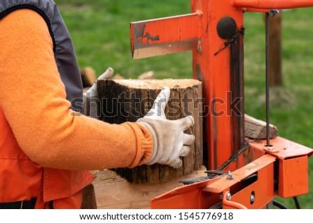 person splitting firewood on a splitter machine, outdoors