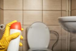 Person spraying air freshener in bathroom