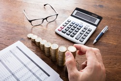 Person Stacking Coins With Calculator And Eyeglasses On Wooden Desk. Income Tax Rise Concept