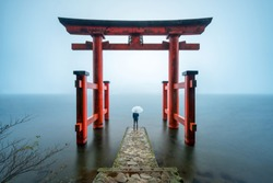 Person standing at the Hakone shrine near lake Ashi, Japan