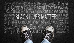 Person standing over Black Lives Matter word cloud with dramatic lighting. Concept of stopping racism against people of color.