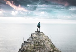Person stands alone and looks around on the edge of  the cliff with vast sea and dramatic sky in the background.  Concept of solitude, adventuree and lifestyle. 2020