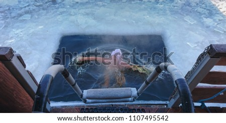 Person surfacing in an ice-hole after a swim in icy water of a river or lake viewed from the top of the exit ladder #1107495542