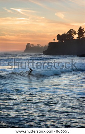 Person surfing at sunset in California.