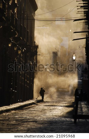 Person sweeping a cobblestone street, Mexico.