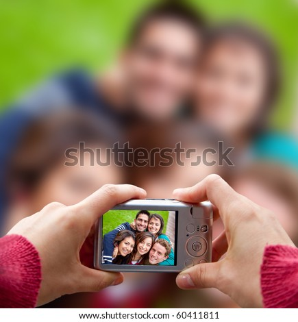 Person taking a picture of a group of friends outdoors