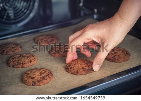 Person taking baked homemade chocolate chip cookie from baking tray. Close up.