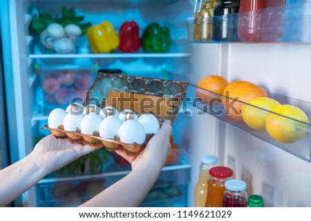 Person taking box with fresh eggs from refrigerator #1149621029