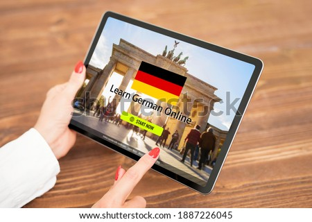 Person taking online courses on tablet to learn German language Photo stock ©