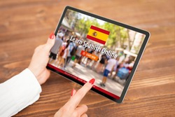 Person taking online courses on tablet to learn Spanish language