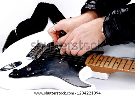 Person tuning a guitar from its headstock over white background - Shutterstock ID 1204221094
