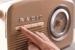 Person tuning retro radio, closeup