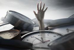 Person under time pressure is stuck between clocks